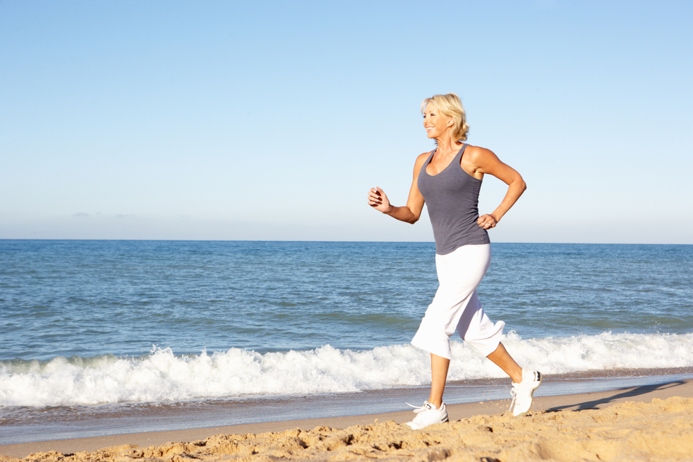 Kelowna Gyms - Fitness over 40 - Onelife Fitness - middle age woman jogging on beach