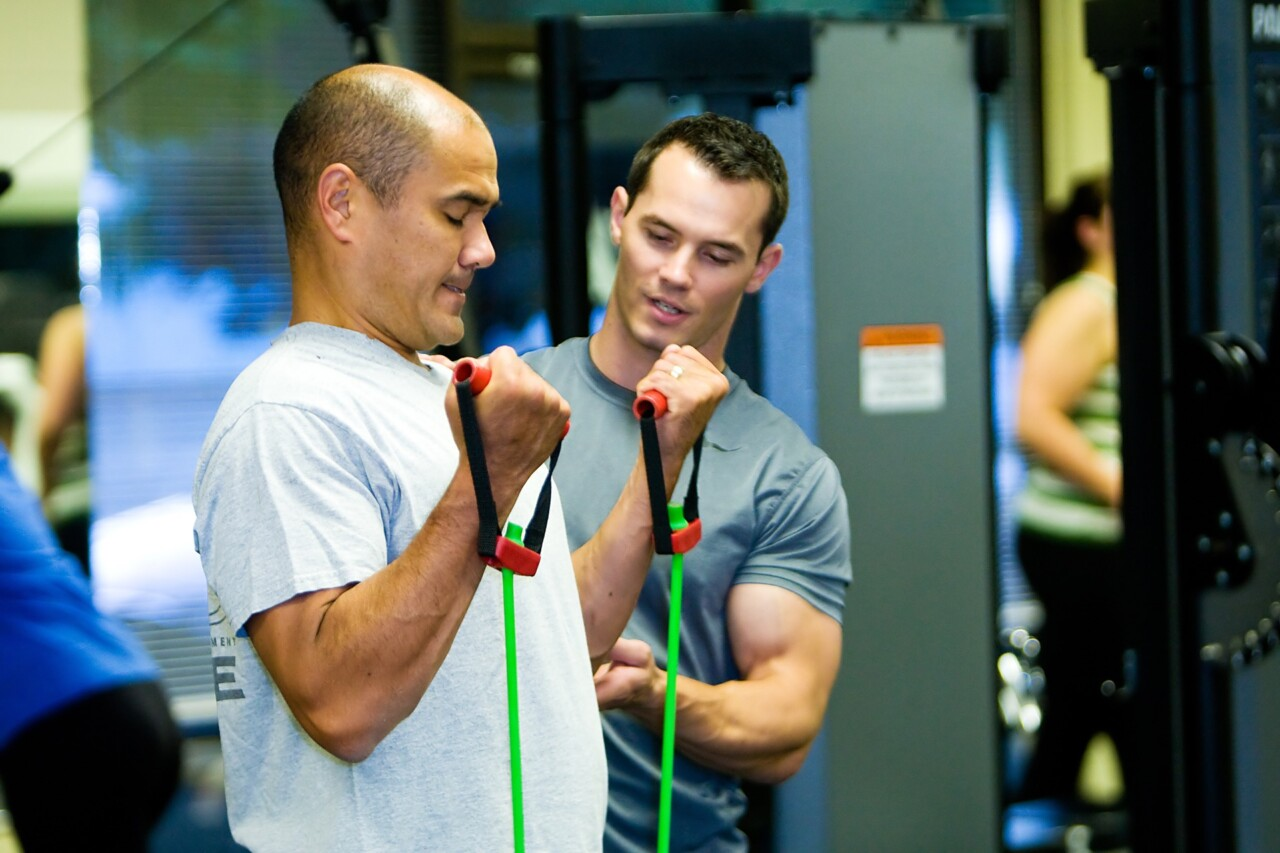 Personal trainer helping older man