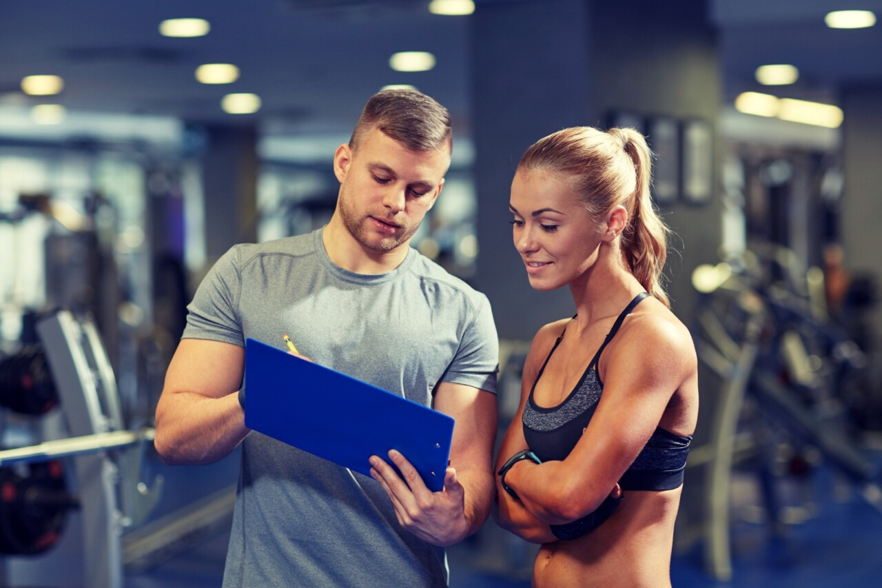 Young woman reviewing results with personal trainer