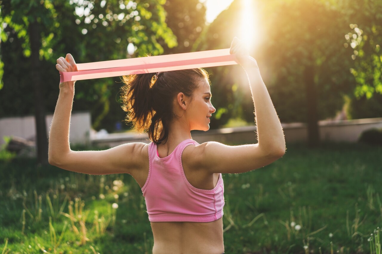 Young woman using a resistance band to work off flabby arms