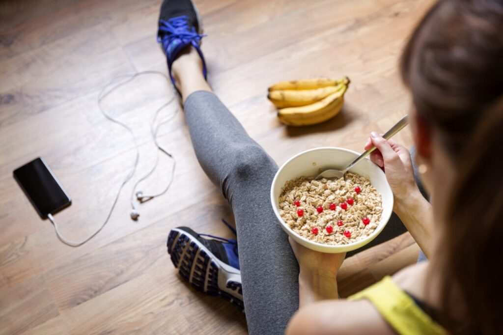 Young woman eating healthy meal after working out