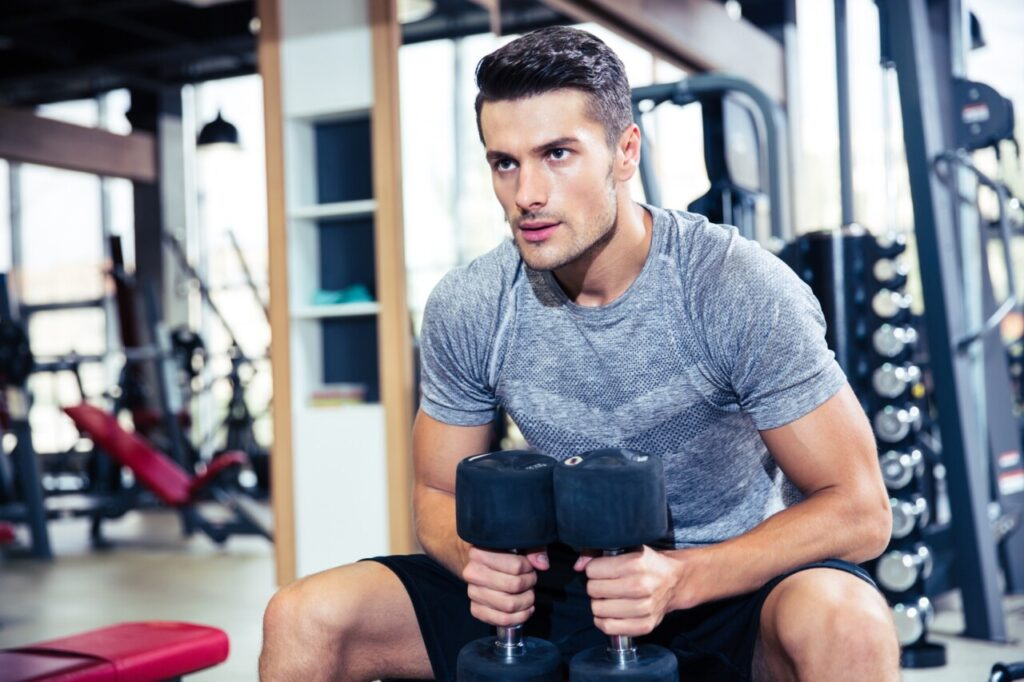 Man working out at gym with dumbbells