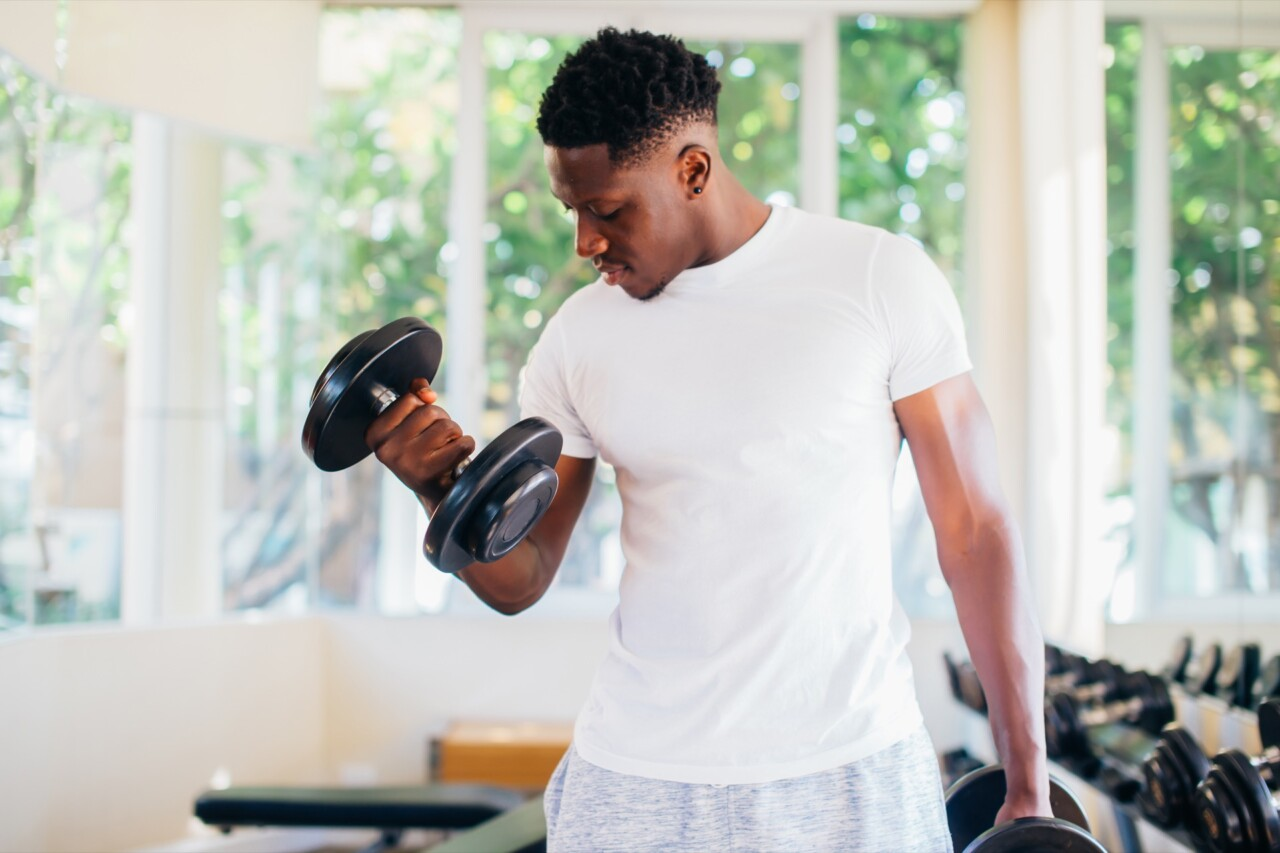 Young black man losing weight by working out in gym after quarantine